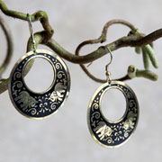 Earrings round black with gold coloured elephants